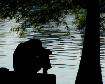 Silhouette of a depressed man by the lake